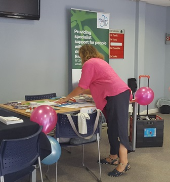 A representative at the Carer's event putting leaflets out on a table